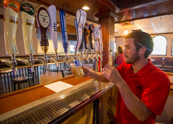 Andy Vavul, co-owner of The Pub in Granger, pours a beer during a soft opening in August 2017. He and his twin brother and co-owner, Pete, have decided to close the business after June 5.