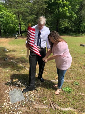 Ted Alexander places a flag on the grave of a veteran in Shelby in 2020.