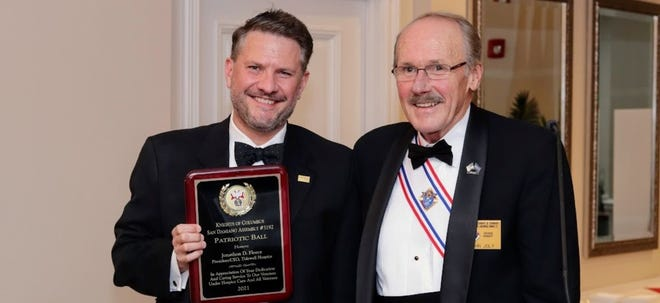 Jonathan Fleece, left, receives the Patriotic Ball Honoree Award from Knights of Columbus representative John Joly, who is also a Tidewell Honors Veterans volunteer.