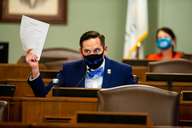 State Rep. Tim Butler, R-Springfield, holds up a copy of the indictment of Tim Mapes during a public hearing with the Illinois House and Senate redistricting committees on the proposed boundaries for new state legislative districts at the Capitol on Wednesday.