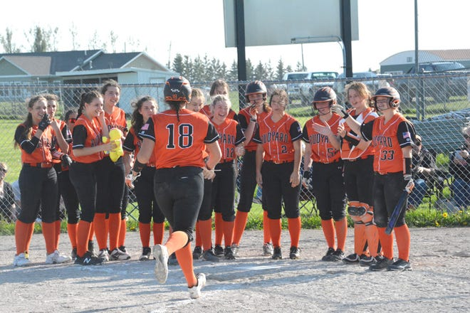 Rudyard's Brooklyn Besteman (18) is greeted at home plate by her teammates following a home run blast at Pickford Tuesday. The Bulldogs swept a softball doubleheader over the Pirates.