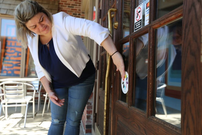 """Joanna Becker, general manager of The Burger Stand, places an """"Inclusive Topeka"""" decal on the restaurant's front door, indicating the business has made a commitment to promoting diversity and inclusion."""