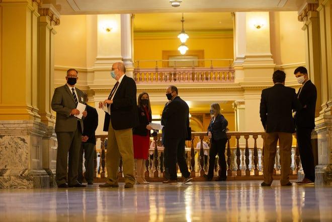 Lobbyists talk around the rotunda of the Kansas Statehouse on Wednesday during the close of the legislative session.