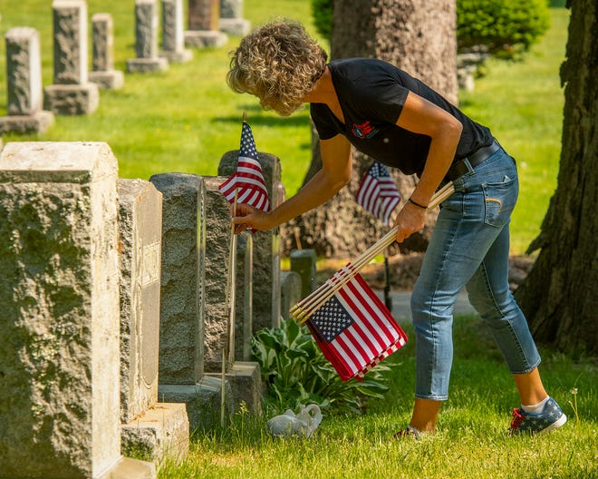 Robyn Coons of West Boylston places American flags on the graves of veterans in St. John's Cemetery Wednesday. Coons participated with the group Project New Hope in placing the flags ahead of Monday's Memorial Day holiday.