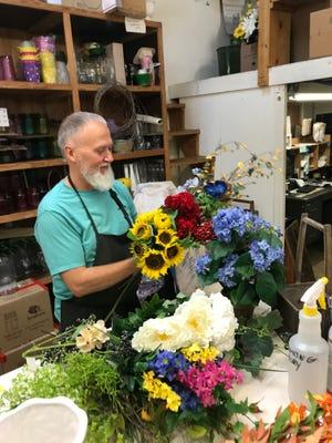 Scott Snow arranges flowers at Scott's on the Square.
