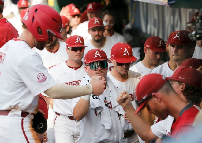 Arkansas players congratulate Arkansas base runner Cullen Smith (14) after he scored a run against Georgia during the SEC Tournament Tuesday, May 26, 2021, in the Hoover Met in Hoover, Alabama. [Staff Photo/Gary Cosby Jr.]