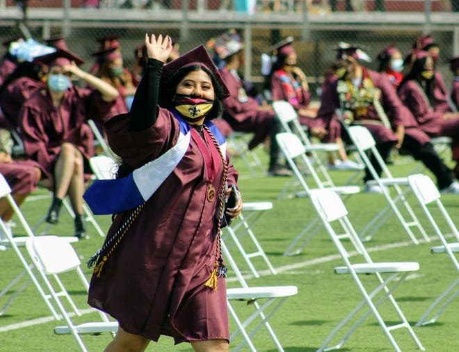 An Adelanto High School student waves to the crowd before receiving her diploma at the school's graduation ceremony on Tuesday, May 25, 2021.