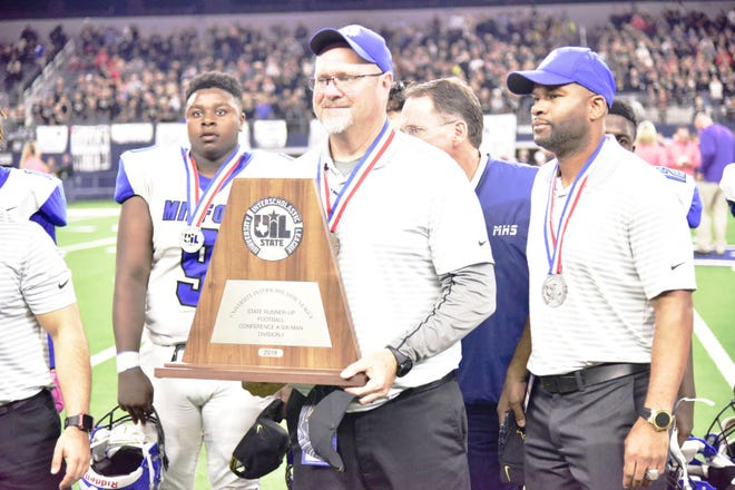 Milford head football coach Ronny Crumpton holds the Class 1A Division I  runner-up trophy at AT&T Stadium in 2018 after the Bulldogs' state final loss to McLean. Crumpton has been reassigned and will not return as head coach in 2021, Crumpton confirmed Wednesday.