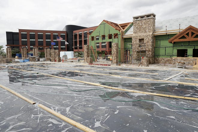 Construction of The Plaza at Gateway Park is progressing on schedule and on budget in downtown Neenah. The plaza's refrigerated ice rink is shown in the foreground, and the Plexus Corp. headquarters is visible in the background.