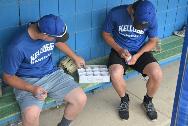Bruins players sign baseballs at C.O. Brown Stadium to give to Kellogg Community College supporters before heading out to the NJCAA Division II World Series.