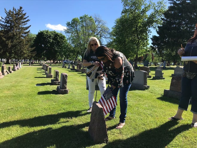 Houses of Honor volunteers Kathy Parker, from left, Teresa Dahl and Samantha Houska place flags Wednesday at the graves of veterans in Allouez Catholic Cemetery ahead of Memorial Day. They were helping American Legion Post 11 Sullivan Wallen Green Bay.