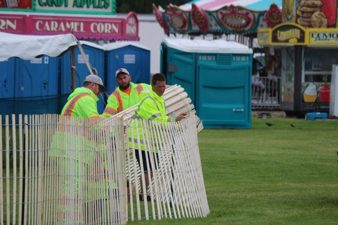 City crew workers assemble fencing around the Walleye Festival area at Waterworks Park in the rain on Wednesday ahead of the event's kickoff Thursday evening.