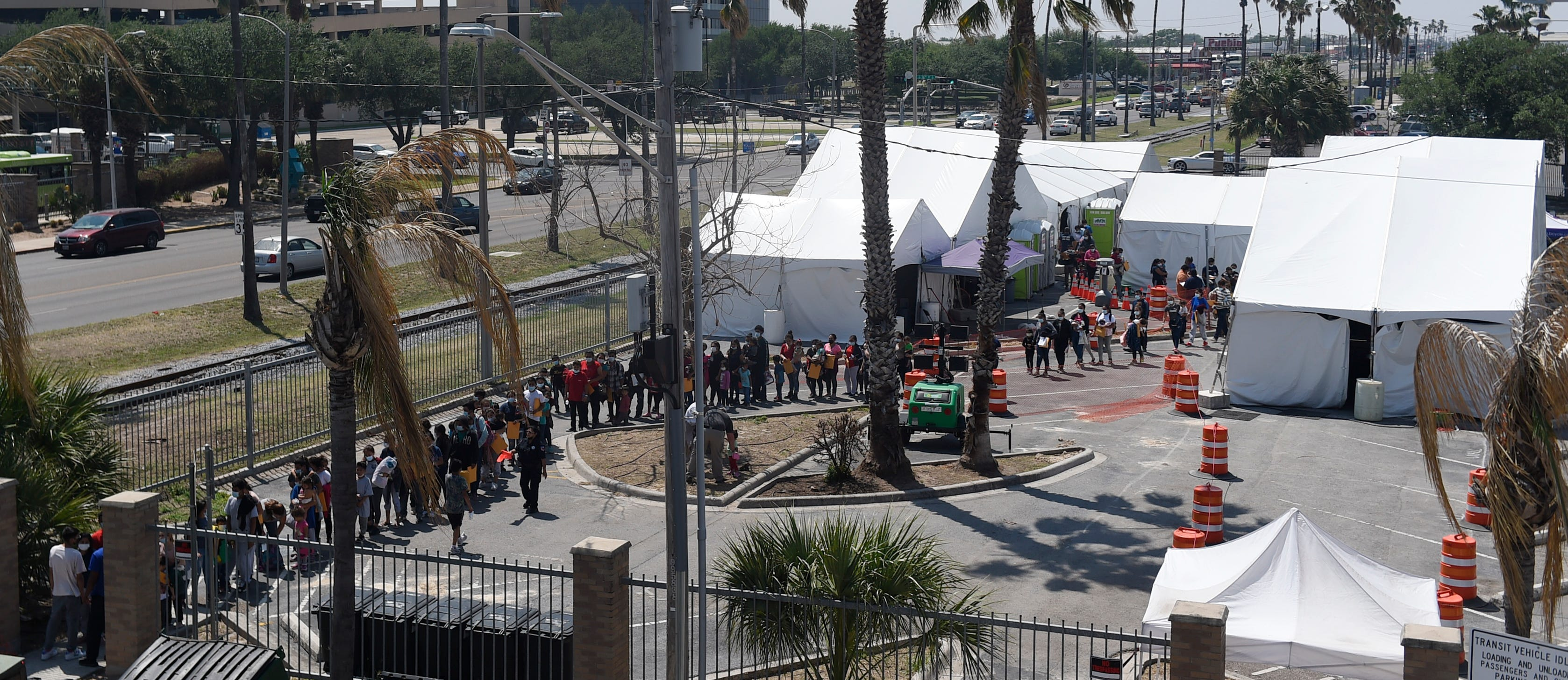 Migrants line up to walk to a bus station April 9 in McAllen, Texas. The tents are for coronavirus rapid testing before people travel to their asylum contacts.