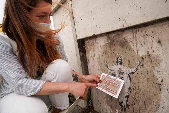 Artist Alessia Babrow holds the Vatican stamps next to her street art during an interview with the Associated Press, at the Vatican, Friday, May 14, 2021.
