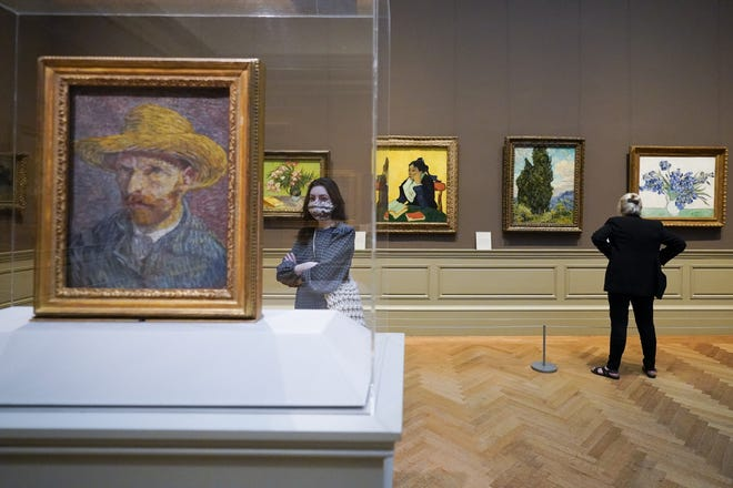 """Visitors to the Metropolitan Museum of Art inspect Van Gogh paintings, April 2, in New York. As we emerge from the lockdowns of the pandemic, we cannot simply """"go back to normal,"""" Jill DeTemple writes.  [AP PHOTO/MARY ALTAFFER]"""