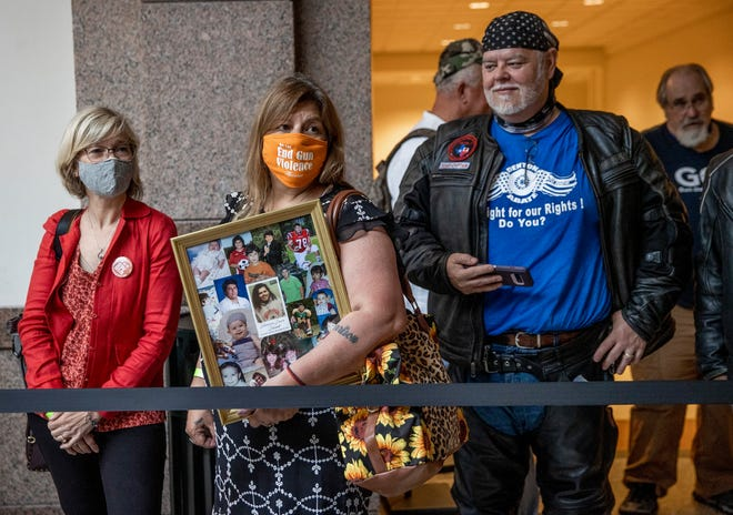 Angelica Halphen of Houston, second from left, waits in line at the Capitol on April 29 to get into a Senate hearing on a bill to allow permitless carry of handguns. Halphen carried photos of her son, Harrison Schmidt, who was shot and killed at age 18 in a road rage incident in 2019.