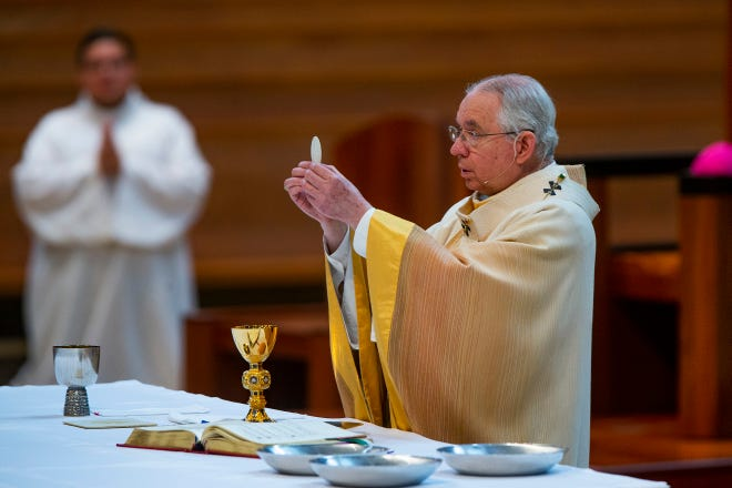 In this Sunday, June 7, 2020 file photo, Archbishop Jose H. Gomez holds a Communion wafer as he celebrates the the Solemnity of the Most Holy Trinity, a Mass with churchgoers present at the Cathedral of Our Lady of the Angels in downtown Los Angeles. Despite calls from some of its members for a delay, the U.S. Conference of Catholic Bishops plans to devote part of its national meeting in June 2021 to the sensitive issue of which Catholics are worthy of receiving Communion.