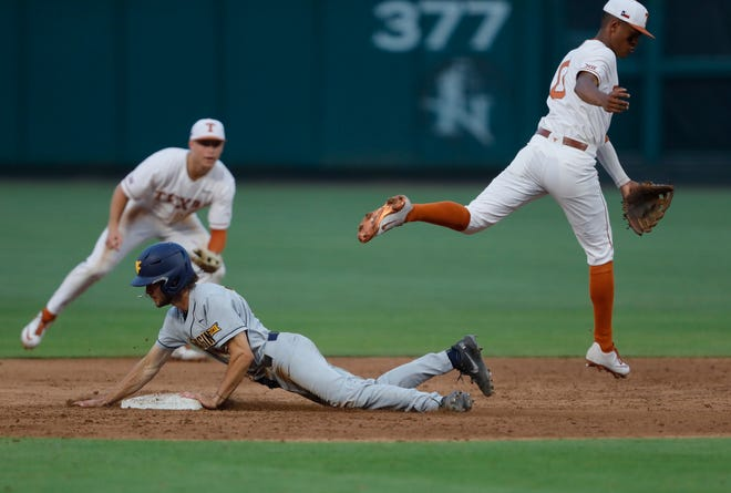 West Virginia's Ben Abernathy slides safely into second base as Texas shortstop Trey Faltine leaps over him during the Mountaineers' 5-1 win Wednesday night at the Big 12 Tournament at Chickasaw Bricktown Ballpark in Oklahoma City.