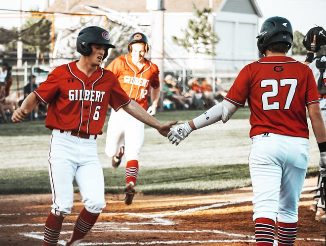 Gilbert's Tucker Hanson gets congratulated by Eli Eldred after scoring a run during the first inning of the No. 1 Tigers' 3-1 victory over North Polk Wednesday at Gilbert.