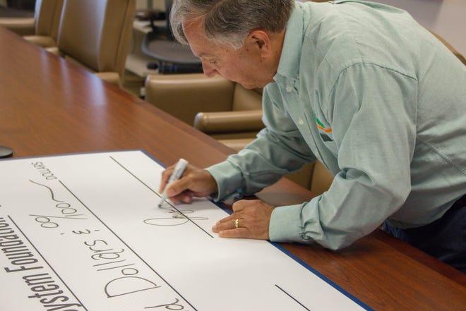 Jay Stine, Owner, Stine, LLC signing the check