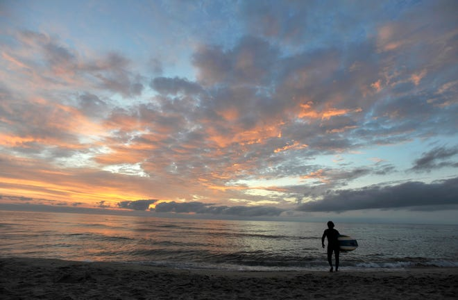 A sunrise surfer heads out to sea at Coast Guard Beach in Eastham.