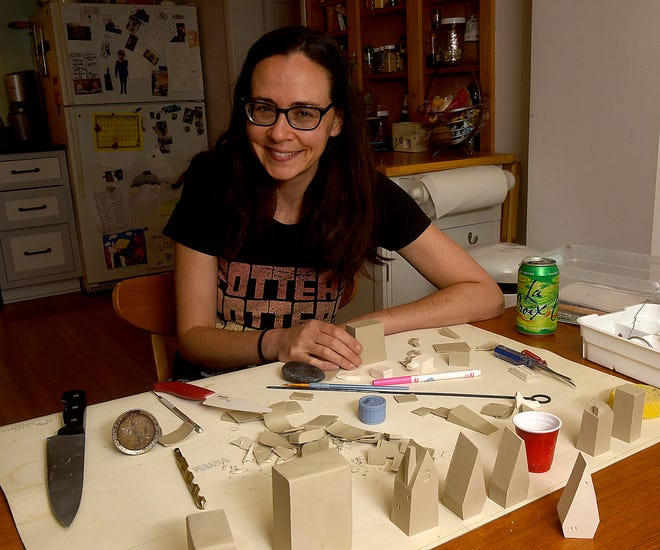 Columbia photographer/artist Katie Barnes works with clay to create tiny ceramic house sculptures.
