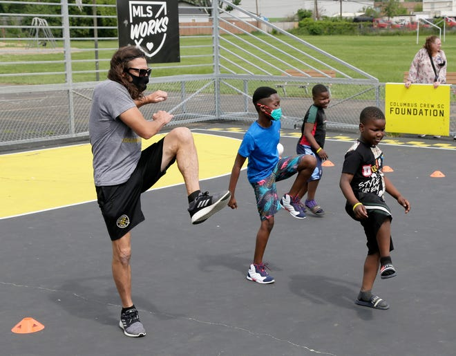Former Columbus Crew player Frankie Hejduk leads students through a warm-up as members of the soccer organization hosted two youth soccer clinics on the mini-pitch at Eakin Elementary School on the West Side, as part of a program put on hold last year because of the COVID pandemic.