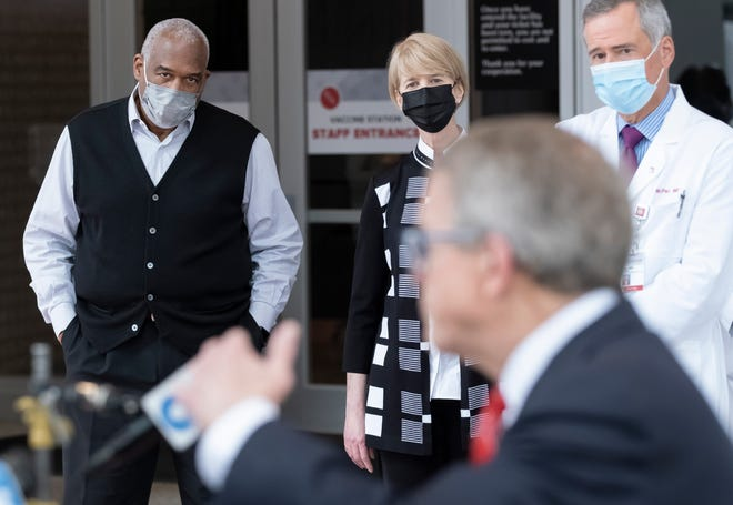 Ohio State athletic diretor Gene Smith, president Kristina Johnson and Wexner Medical Center CEO Harold Paz listen to Gov. Mike DeWine speak after he toured the COVID-19 mass vaccination facility set up at Ohio State's Schottenstein Center on March 9.
