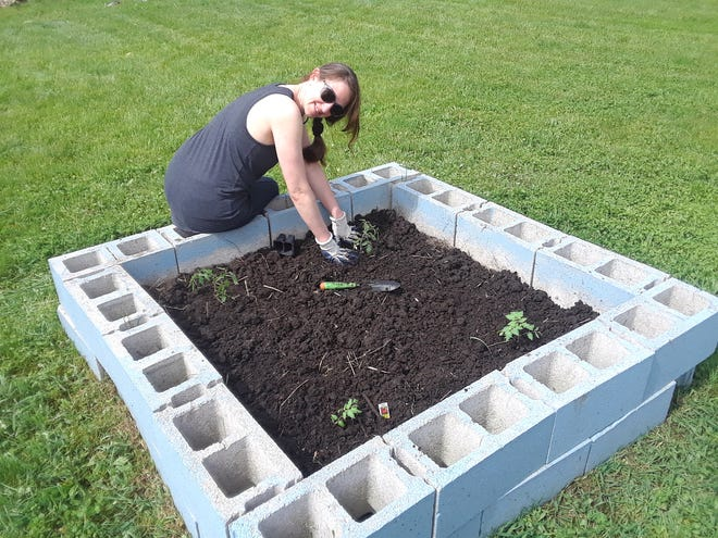 Christie Boxer, an Adrian resident and one of the main caretakers of the Adrian Community Garden, is shown tending to one of the raised flowers boxes during last year's community planting day. The 2021 planting day at the community garden is scheduled for 9 a.m. to noon on Saturday, May 29.