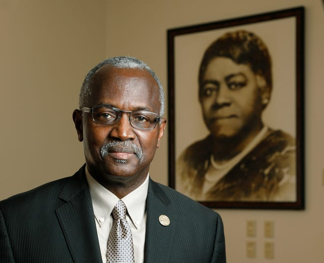 Bethune-Cookman University Interim President Hiram Powell poses next to a photo of the school's founder, Mary McLeod Bethune. Powell says he draws inspiration from Bethune's life, her famous Last Will and Testament and her legacy.