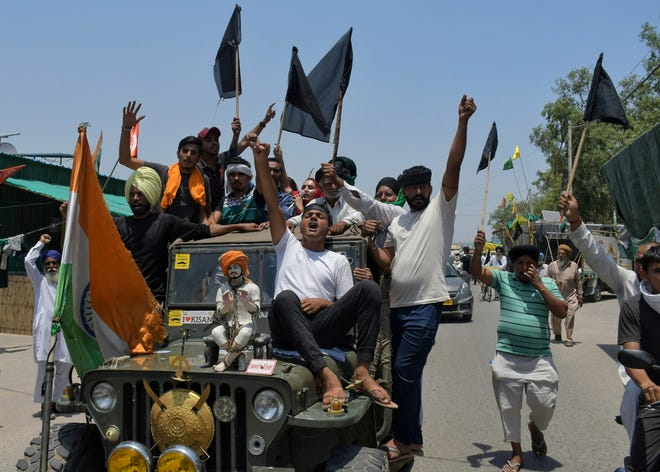 Farmers, some carrying black flags, on a vehicle during a protest in Ghazipur, outskirts of New Delhi, India, on May 26. Indian farmers demanding the government repeal new agriculture laws they say will devastate their livelihoods marked their protest movement's sixth month May 26 by flying black banners on the cars and tractors and burning effigies of the prime minister.