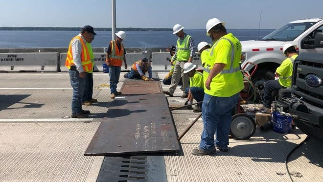 Workers drop temporary steel plates atop the protruding metal expansion joint edges after Thursday's southbound Buckman Bridge closure, with more permanent repairs expected soon, the FDOT said.