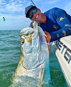 Capt. Tyler Kapela, of Hit and Run Fishing Charters of Tierra Verde, shows off a tarpon he and a client caught off St. Petersburg beach last week.