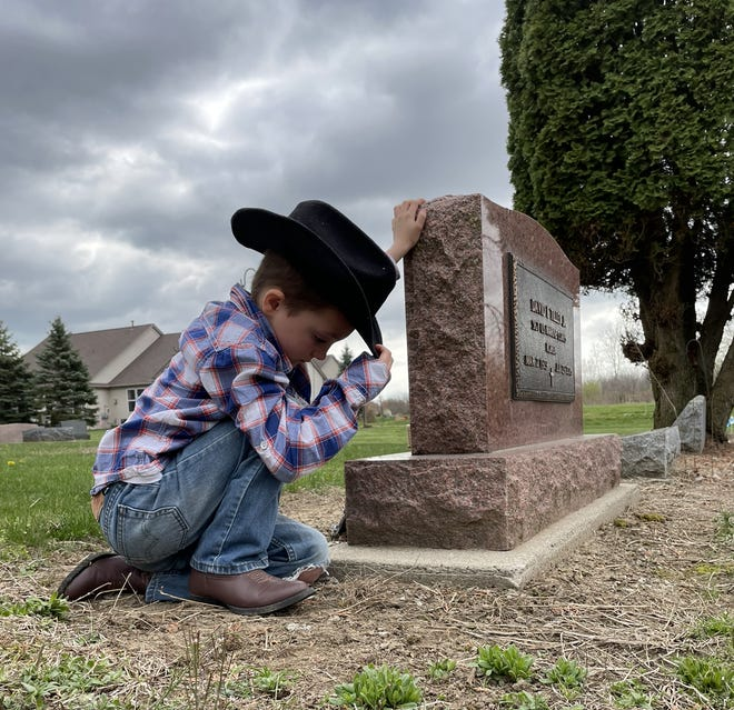 Brantley Tilley, 7, of Milan kneels next to the grave of his great-grandfather, Sgt. David L. Tilley Jr., who served in the Marines Corps until the day he died. His father, David Tilley, who was named after his Marine grandfather, said his two sons always want to stop by the cemetery, located in South Rockwood, to pay their respects.
