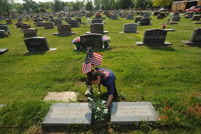 Anthony Bowser, then 8, places flowers on the graves of veterans at St. Joseph Cemetery. The cemetery plans to more strictly enforce its decoration policies.