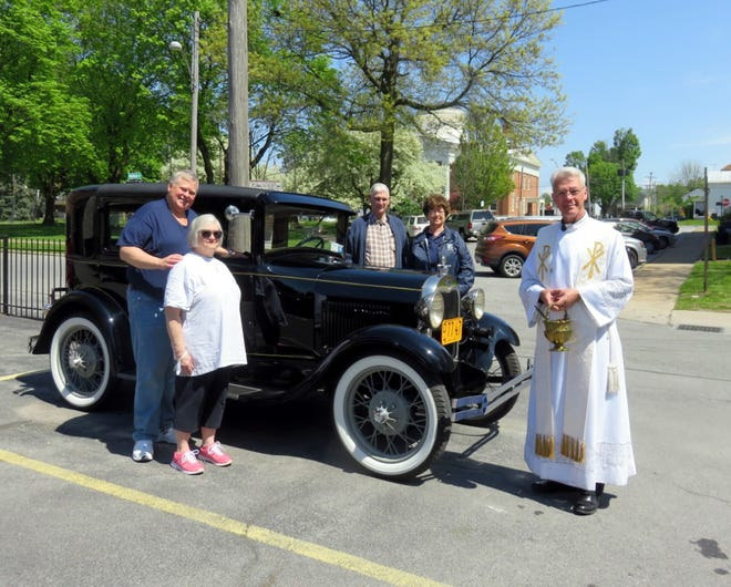 Posing during the Mohican Model A Ford Club's May 15 meeting at St. Peter's Roman Catholic Church in Rome are, from left, hosts Pat Abbott and Sharon Abbott; Elwyn Smith, the owner of the 1929 Model A Ford; club secretary and photographer Mabel Silliman and Rev. Sean O'Brien, who blessed the cars.