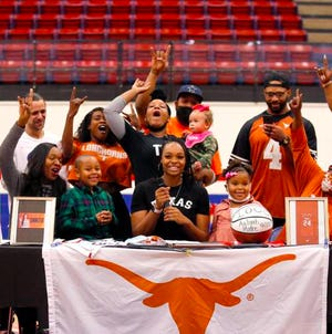 Aaliyah Moore celebrates with her family before signing with Texas during a signing day ceremony at Moore High School in Moore, Okla.,  Wednesday, Nov. 11, 2020. [Sarah Phipps/The Oklahoman]