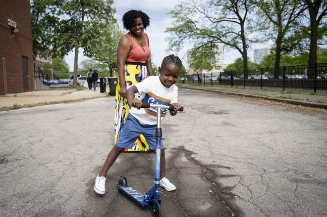 """Gus """"Jett"""" Hawkins, 4, plays with mother, Ida Nelson, on May 21 in Chicago. Nelson got a call from his school informing her his braids were against the school dress code."""