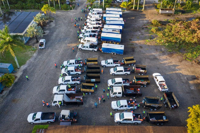 Landscape maintenance vehicles are lined up in Heritage Farms west of Lake Worth Beach.