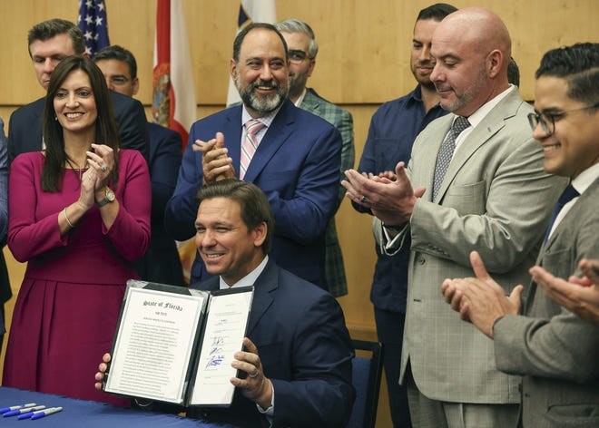 Gov. Ron DeSantis holds up the signed legislation that seeks to punish social media platforms that remove conservative ideas from their sites, at Florida International University in Miami on Monday.