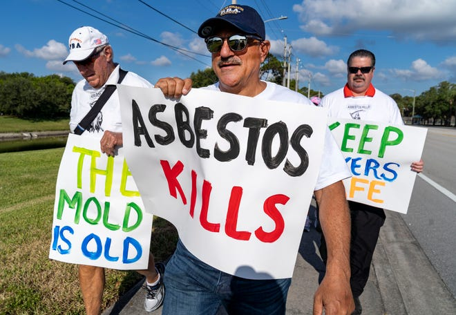 John Kazanjian, Palm Beach County Police Benevolent Association President, center, marches with PBSO employees and supporters outside the police headquarters in suburban West Palm Beach, Florida on May 27, 2021. They are concerned that building renovations are exposing them to asbestos and black mold.