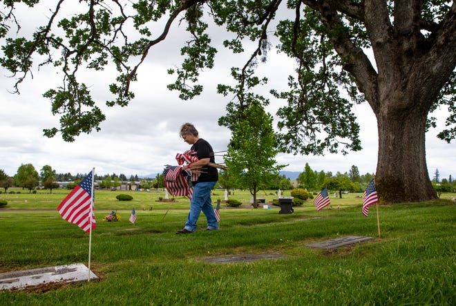 Dee Harbison, who has been funeral director in Lane County for 26 years, leads a crew of a dozen volunteers in placing United States Flags on the graves of service members at Lane Memorial Gardens in Eugene for Memorial Day. The informal committee that she is involved with oversee five area cemeteries The group made the decision to forgo in-person ceremonies for the second year in a row because of COVID-19, but moved ahead with placing flags this week. She estimates they will plant over 2000 flags in Lane Memorial Gardens alone over two days.