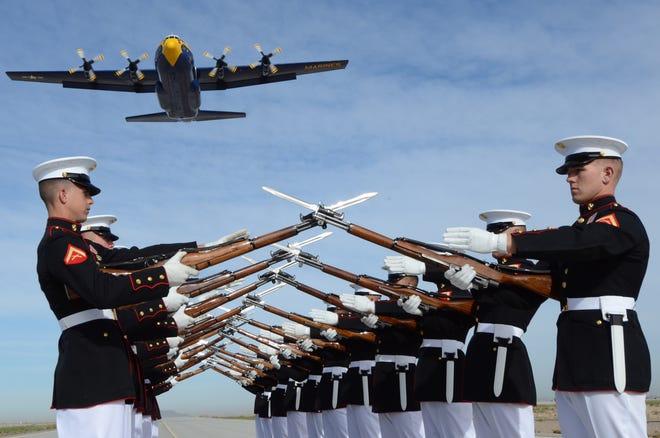 """U.S. Marine Corps Silent Drill Platoon performs while the Blue Angels C-130 Hercules, """"Fat Albert,"""" flies overhead aboard Marine Corps Air Station Yuma, Ariz., on March 4, 2014. The Silent Drill Platoon will visit Canton on June 2. (U.S. Marine Corps photo taken by LCpl. AaronJames B. Vinculado/Released)"""