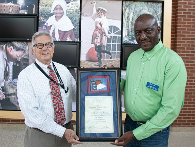 Tryon Palace Executive Director Bill McCrae stands with long-time employee Keith McClease who was given the Caswell Award for his 45 years' service.