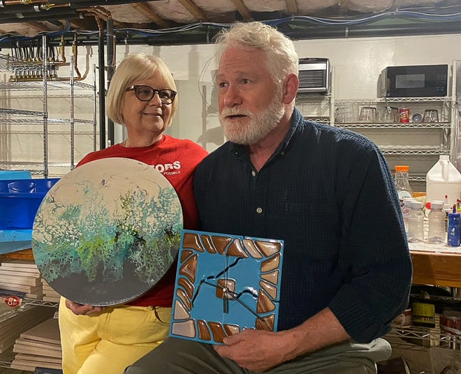 Chris and Cindy Payne in their Brimfield basement where each has space to work on the crafts they enjoy. Cindy, once a soap maker, now creates acrylic pour paintings while Chris creates art with heated glass.
