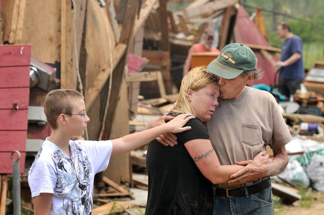 Ron Weston, right, comforts his daughter, Heather Dickinson, as Heather's son, Devin Dickinson, looks on yesterday in Brimfield. Mr. Weston's farm - Mrs. Dickinson's childhood home - was destroyed.