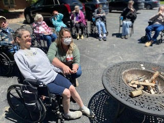 Springs Valley Meadows Director of Nursing Brooke Ball helps resident Rachel Brown roast a marshmallow during Nursing Home Care Week's Fall Festival.