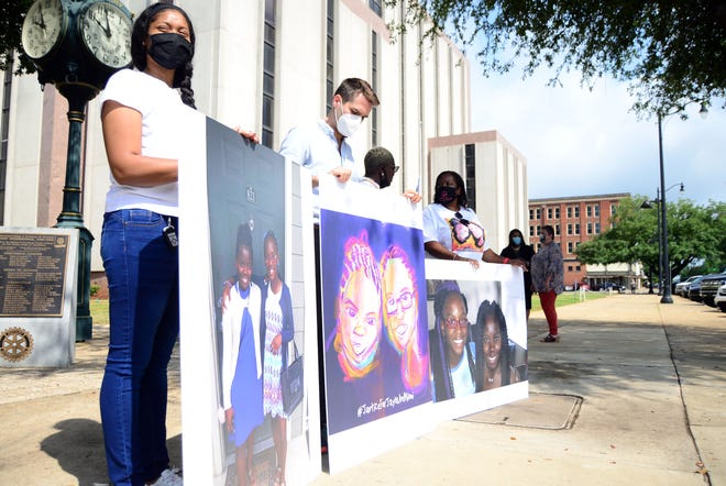Enlarged photos of 13-year-old Jayla Parler and 11-year-old Niomi James are held outside the Tuscaloosa County Courthouse by friends and family on Thursday, May 27, 2021. The girls were killed in a DUI crash of an ex-astronaut that occurred nearly five years before.