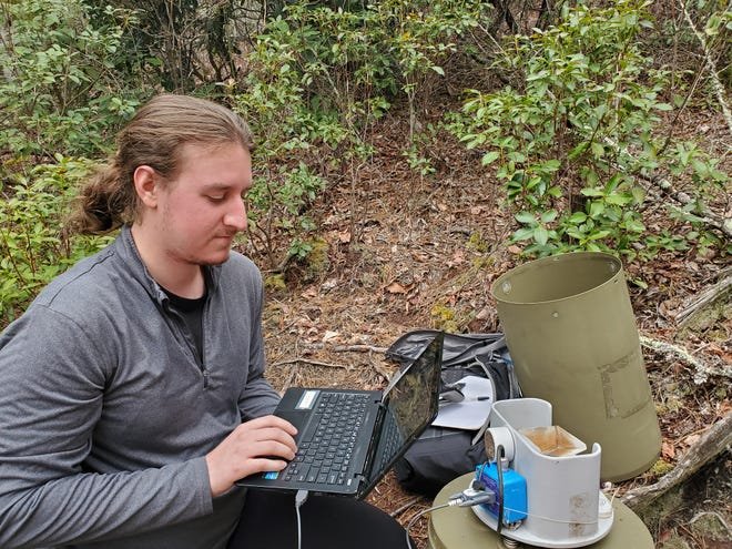 Mountain Rainger Samuel Peterson transfers data from rain gauge logger to laptop.