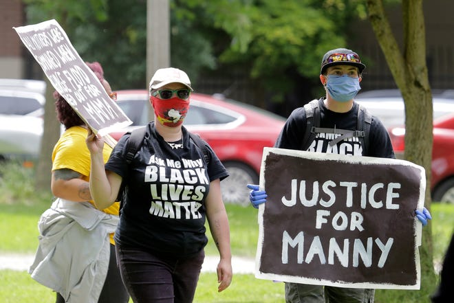 """FILE - A protester holds a sign that reads """"Justice for Manny"""" in this June 5, 2020 file photo in Tacoma during a protest against police brutality. On Thursday, the Washington state attorney general filed criminal charges against three police officers in the death of Manuel Ellis, a Black man who died after telling the Tacoma officers who were restraining him he couldn't breathe."""